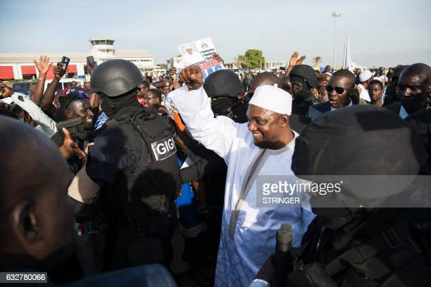 Gambia's new president Adama Barrow gestures as he arrives at Banjul airport on January 26 2017 in Banjul after returning from Senegal Jubilant...