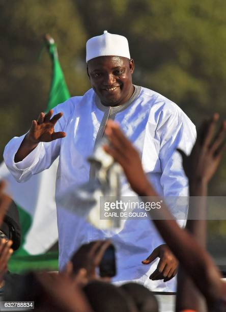 Gambia's new president Adama Barrow waves to supporters as he leaves the airport in Banjul on January 26 after returning from Senegal Jubilant...