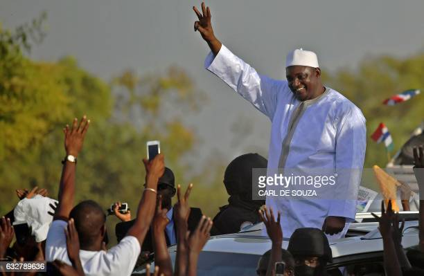TOPSHOT Gambia's new president Adama Barrow waves to supporters as he leaves the airport in Banjul on January 26 after returning from Senegal...