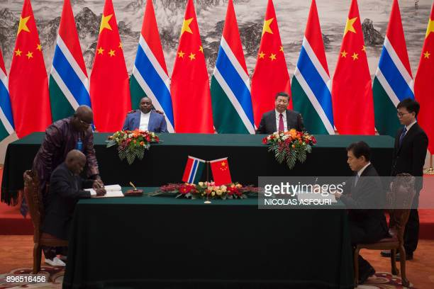 Gambia's President Adama Barrow and China's President Xi Jinping look on during a signing ceremony between the two countries at the Great Hall of the...