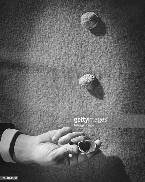 A gambler hiding the pea in his hand during the shell game