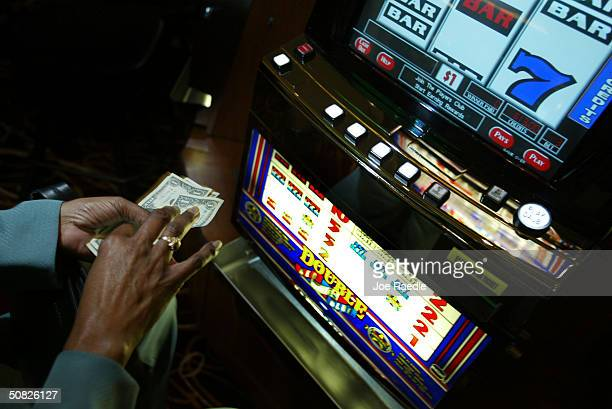A gambler prepares to put her money in a slot machine May 11 2004 during the grand opening for the Seminole Hard Rock Hotel and Casino in Hollywood...