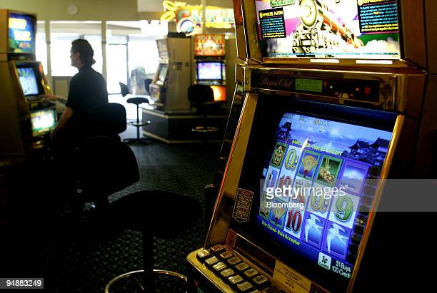 A gambler trys his luck on one of the poker/slot machines in Belfield Hotel's gaming room in Sydney's western suburbs November 30 2003