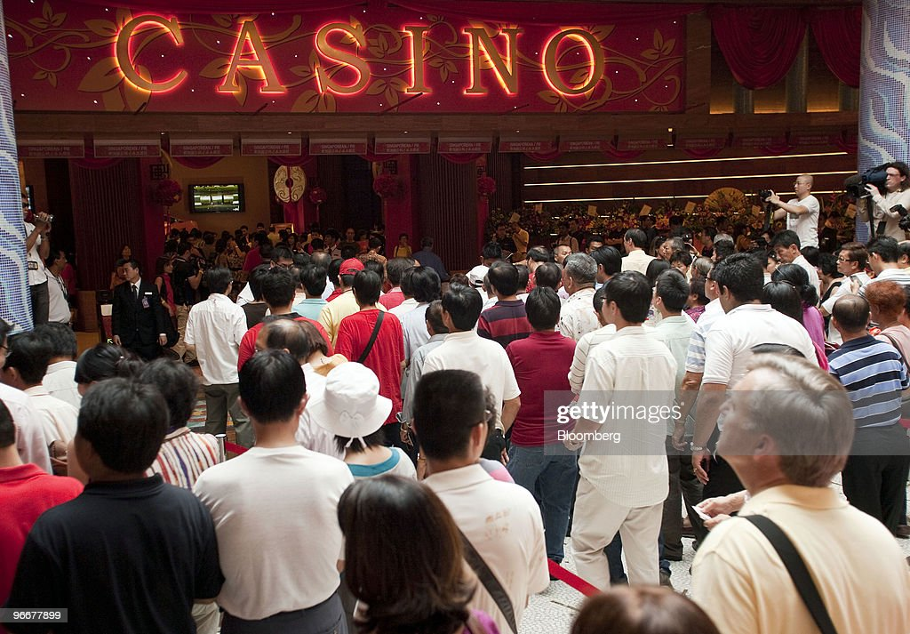 Gamblers line up to enter the casino at Genting Singapore Plc's Resorts World Sentosa on its first day of operation, in Singapore, on Sunday, Feb. 14, 2010. Genting Singapore Plc, the unit of Asia's largest publicly traded gambling operator, opened the country's first casino as Lunar New Year celebrations commenced. Photographer: Charles Pertwee/Bloomberg via Getty Images