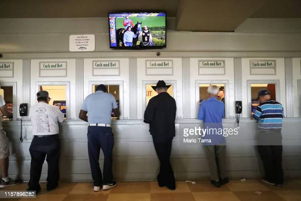 Gamblers stand at betting windows on the final day of the winter/spring horse racing season at Santa Anita Park on June 23, 2019 in Arcadia,...