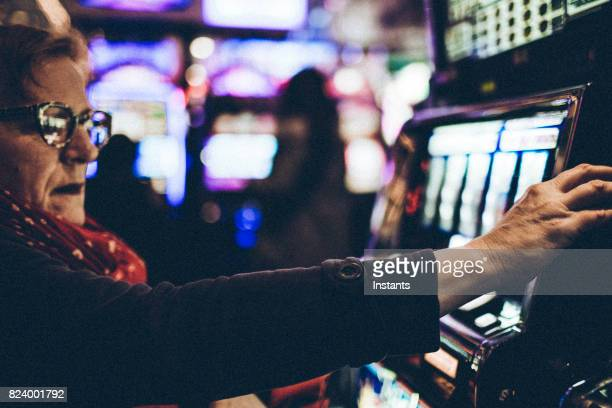 Gambling 59 year old woman playing a slot machine in one of Las Vegas casinos.