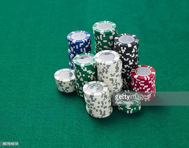 gambling chips on green felt table - gambling table stock pictures, royalty-free photos & images