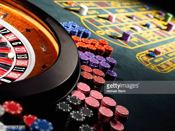 gambling chips stacked around roulette wheel on gaming table - casino stock pictures, royalty-free photos & images