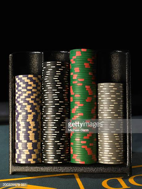 gambling chips stacked in dispenser on gaming table, close-up - gambling table stock pictures, royalty-free photos & images