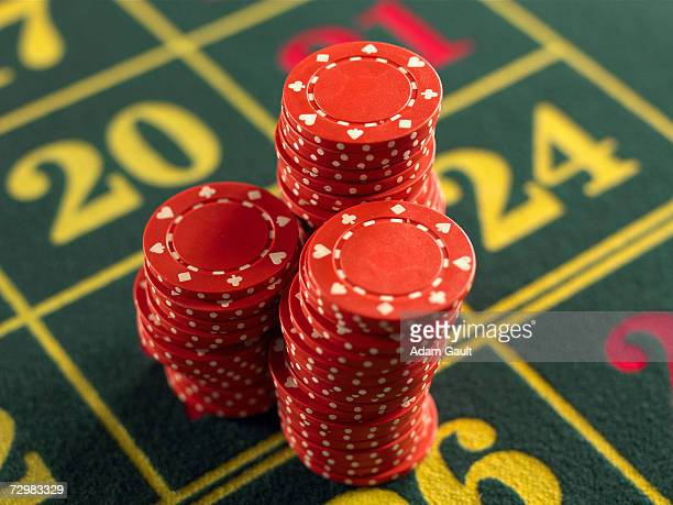 Gambling chips stacked on Roulette table in casino, close-up, elevated view