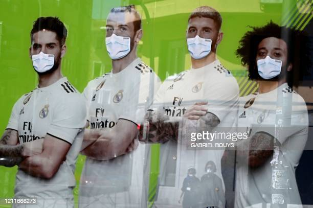 A gambling hall's advertising poster depicting Isco Gareth Bale Sergio Ramos and Marcelo wearing face masks is pictured in Madrid on May 3 2020 amid...