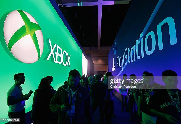 Game enthusiasts and industry personnel walk between the Microsoft XBox and the Sony PlayStation exhibits at the Annual Gaming Industry Conference E3...