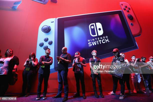 Game enthusiasts and industry personnel walk past the Nintendo Switch exhibit during the Electronic Entertainment Expo E3 at the Los Angeles...