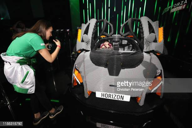 Game enthusiasts and industry pose for a photograph inside a ' 'Forza Horizon 4: LEGO Speed Champions' car during the E3 Video Game Convention at the...