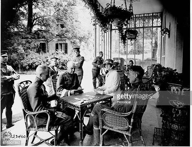 A game of bridge is in progress on the veranda of the Chateau de Villgenis between wounded officers and Mrs WE Corey wife of the American steel...