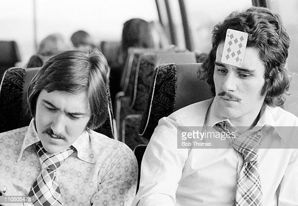 Game of cards passes the time during the long coach journeys to away matches for Northampton Town players Barry Tucker and John Gregory, circa 1974.