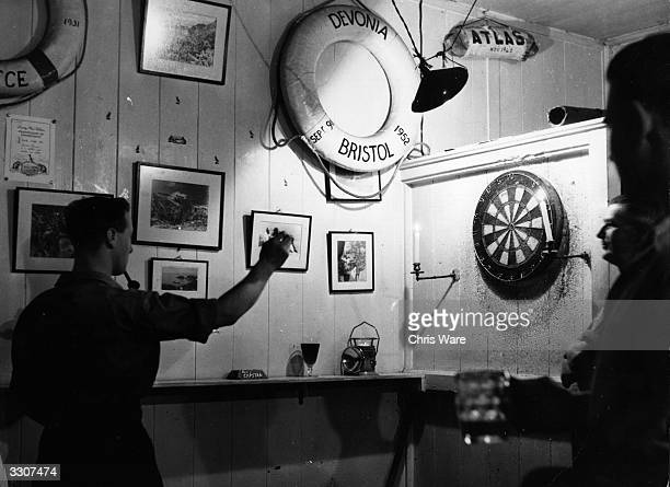 Game of darts being played in a public house.