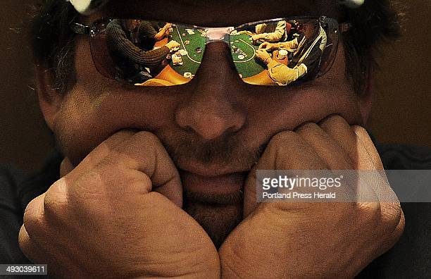 A game of Texas Hold 'Em is relfected in the glasses of Keith Wickerson of Bradford during the first day of table games at the Hollywood Casino in...
