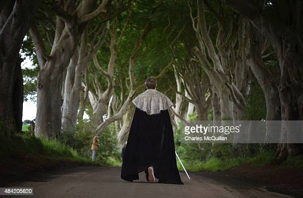 Game of Thrones tourist dressed in costume walks along a beech tree lined road known locally as The Dark Hedges on August 13, 2015 in Belfast,...