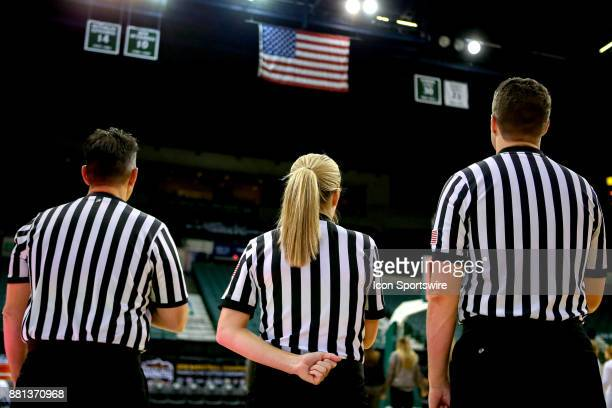 Game officials Frank Steratore Jenna Schroeder and Zachary Klein look up to the flag during the playing of the National Anthem prior to the women's...