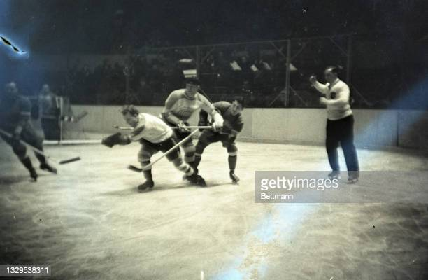 Game play shows McVeigh, of the Americans; Brydge, of the Americans, and Weiland, of the Redwings, fighting for the puck.