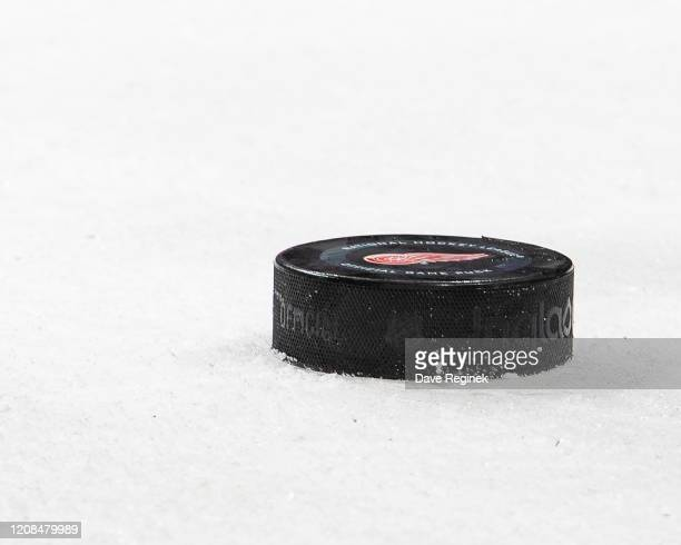 Game puck sits on the ice on a play stoppage during an NHL game between the Detroit Red Wings and the Calgary Flames at Little Caesars Arena on...