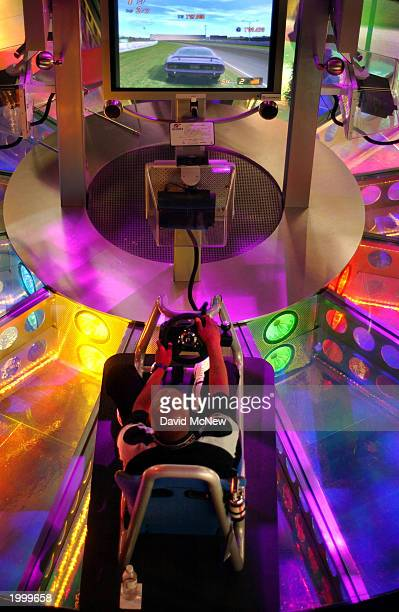 A gamer competes in a race with other gamers on a PlayStation Gran Turismo 4 driving simulator at Interactive Digital Software Association's E3 Expo...
