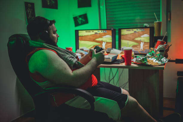 gamer playing video games - fat gamer stock pictures, royalty-free photos & images