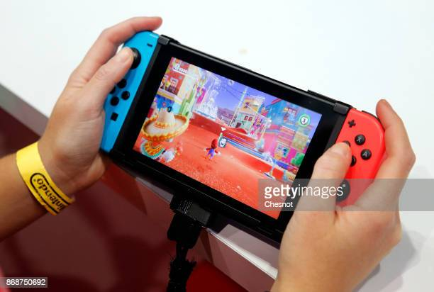 Gamer plays the video game 'Super Mario Odyssey' developed and published by Nintendo on a Nintendo Switch games console during the 'Paris Games Week'...