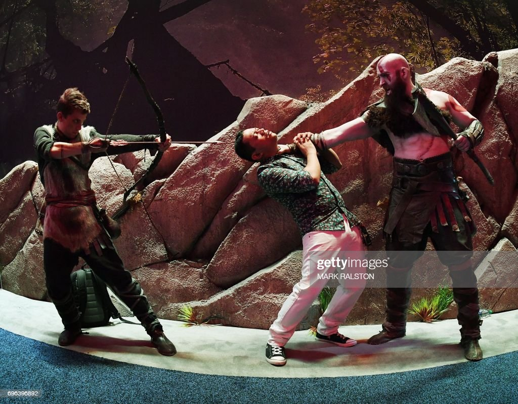 A gamer poses with characters from the 'Uncharted: The Lost Legacy' game at the Los Angeles Convention center on day three of E3 2017, the three day Electronic Entertainment Expo, one of the biggest events in the gaming industry calendar, in Los Angeles, California on June 15, 2017. / AFP PHOTO / Mark RALSTON