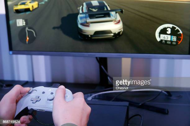 A gamer uses a joystick as he plays the video game 'Forza Motorsport 7' developed by Turn 10 Studio and published by Microsoft Studios on a Microsoft...