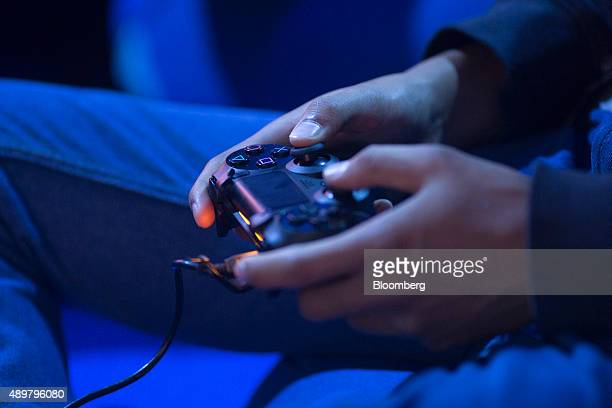 A gamer uses a Sony Corp Playstation 4 controller to play a video game at EGX 2015 video gaming conference in Birmingham UK on Thursday Sept 24 2015...