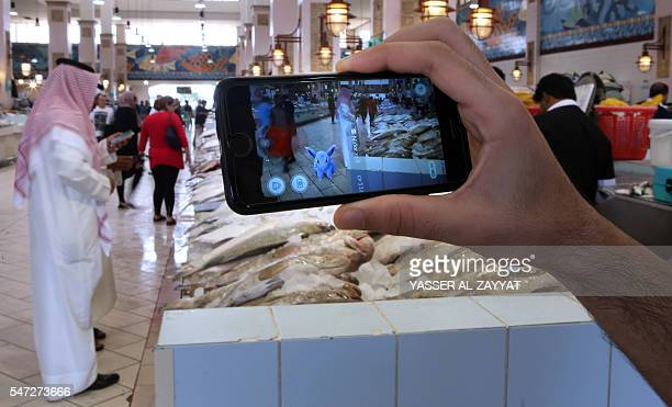 TOPSHOT A gamer uses the Pokemon Go application on his mobile in the main fish market in Kuwait City on July 14 2016 ZAYYAT