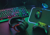 gamer work space concept, top view a gaming gear, mouse, keyboard, joystick, headset, mobile joystick, in ear headphone and mouse pad on black table background.