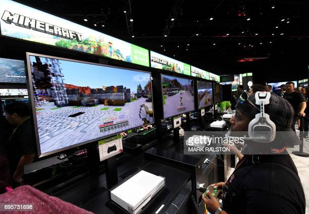 Gamers in the Microsoft Xbox exhibit play the 'Minecraft' game at the Los Angeles Convention center on day one of E3 2017 the three day Electronic...