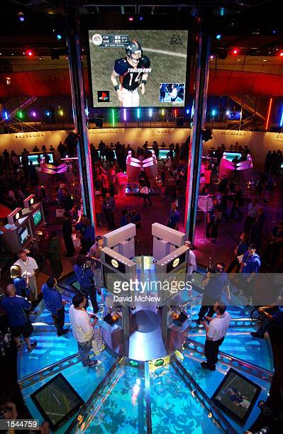 Gamers in the Playstation exhibit area play an electronic football game against players in Florida on the first day of E3, the Electronic...