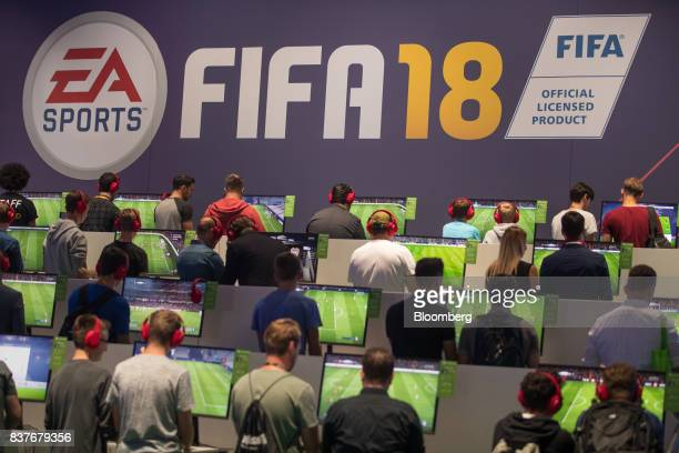 Gamers play the FIFA 18 computer soccer game on the Electronic Arts Inc exhibition stand at Gamescom video games trade fair in Cologne Germany on...