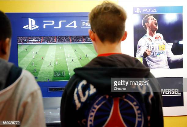 Gamers play the video game 'FIFA 18' developed and published by Electronic Art on a Sony PlayStation game consoles PS4 Pro during the 'Paris Games...