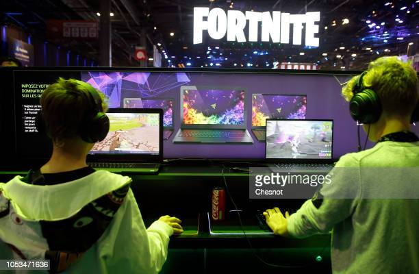 Gamers play the video game 'fortnite' developed by Epic Games on a laptop from the Razer company during the 'Paris Games Week' on October 25, 2018 in...
