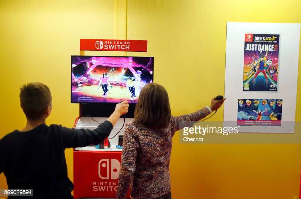 Gamers play the video game 'Just Dance 2018' developed and published by Ubisoft on a Nintendo Switch games console during the 'Paris Games Week' on...
