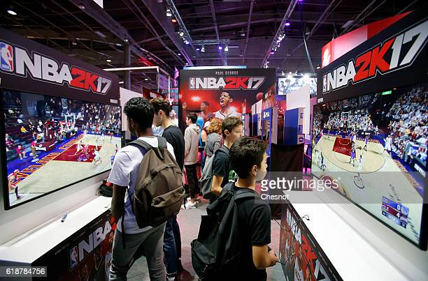 Gamers play the video game NBA 2K 17 developed by Visual Concepts and published 2K Sports on Sony PlayStation game consoles PS4 during the Paris...