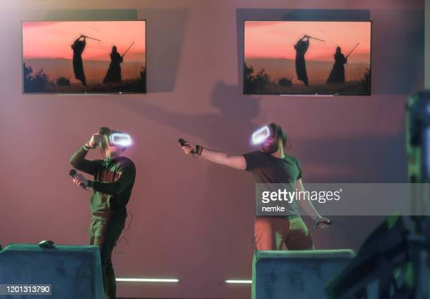 gamers playing vr fighting game at futuristic visitor centre - esports stock pictures, royalty-free photos & images