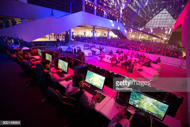 Gamers wearing headphones play video games on desktop computers as attendees watch at the Dreamhack digital festival in Moscow Russia on Saturday Dec...