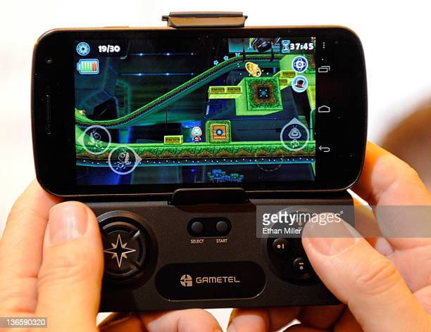 Gametel wireless controller by Fructel is used to play a video game on a smartphone during a press event at The Venetian for the 2012 International...