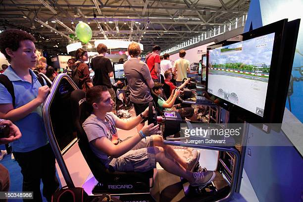 Gaming enthusiasts play Grand Turismo at the Gamescom 2012 gaming trade fair on August 16 2012 in Cologne Germany Gamescom is Europe's largest gaming...