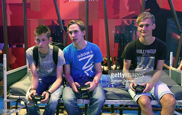 Gaming enthusiasts try out games on the new Sony Playstation 4 at the Gamescom 2013 gaming trade air on August 22 2013 in Cologne Germany Gamescom is...