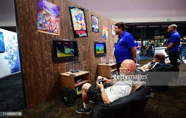 Gaming fans play games on the Sega Genesis Mini Console in a recreated living room section at the 2019 Electronic Entertainment Expo, also known as...