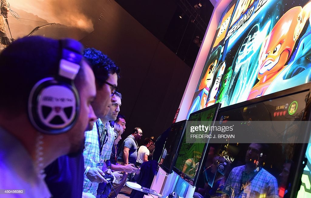 Gaming fans play Lego's 'Batman 3: Beyond Gotham' at the annual E3 video game extravaganza in Los Angeles, California on June 11, 2014, where new consoles from Microsoft and Sony are girding to battle for the throne of the video game industry in the internet age. AFP PHOTO/Frederic J. BROWN