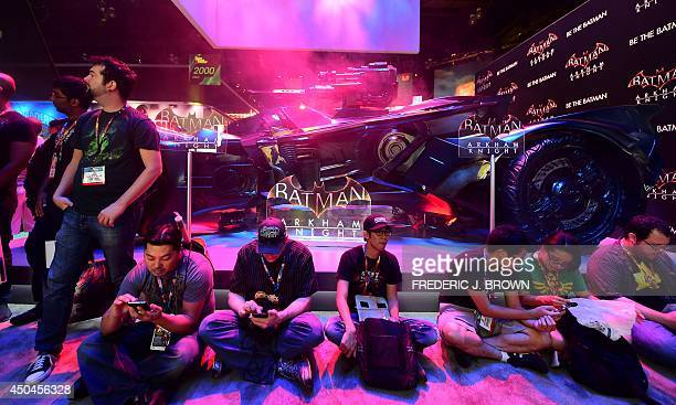 Gaming fans take a break beside the Batman 'Arkham Knight' vehicle displayed at the annual E3 video game extravaganza in Los Angeles California on...