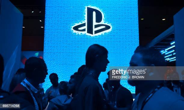 Gaming fans walk past a logo at the Playstation games section at the Los Angeles Convention Center on day one of E3 2017, the three day Electronic...